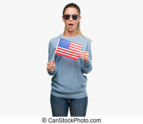 Beautiful young woman holding USA flag scared in shock with a surprise face, afraid and excited with fear expression