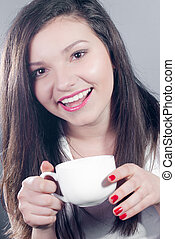 Beautiful young woman holding white cup
