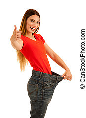 beautiful young woman holds too big trousers as she lost weight