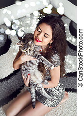 Beautiful young woman hugging and holding cat over boker...