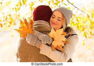 young woman hugging her boyfriend in fall