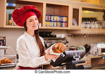Please enjoy. Beautiful young female baker in a lovely hat stretching out a paper package with bread to customer and smiling while standing against checkout counter