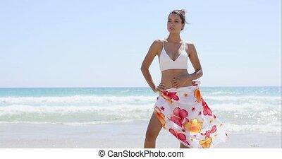 Beautiful young woman in a bikini on the beach