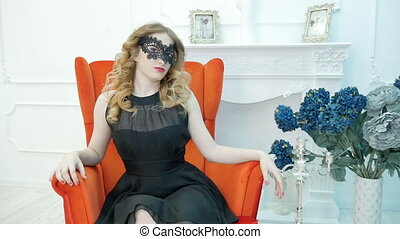 Beautiful young woman in a black carnival mask, at a party, in a red armchair.