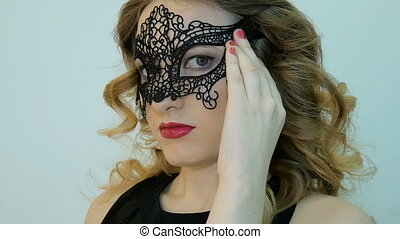 Beautiful young woman in a black carnival mask, at a party.