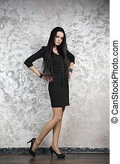 Beautiful young woman in a black dress on abstract gray background
