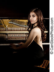 beautiful young woman in a black dress with an open back standing nere the piano on a dark background
