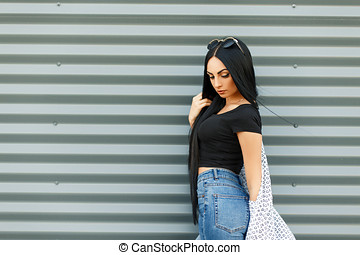 Beautiful young woman in a black stylish T-shirt and blue jeans with high waist posing near a metal wall
