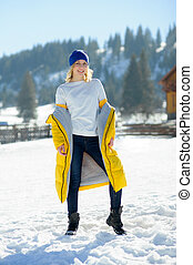 Beautiful young woman in a bright yellow down-padded coat...