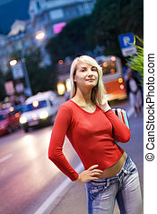 Beautiful young woman in a city at night