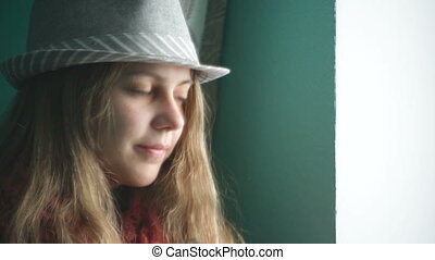 Beautiful young woman in a hat looking out the window