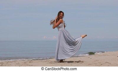 Beautiful young woman in a long dress dancing on the beach ...