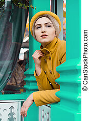 Beautiful young woman in a mustard-colored coat and cap