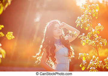 beautiful young woman in a park in spring last rays of the sun