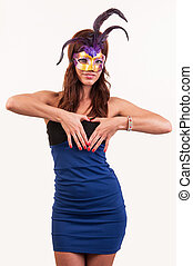 beautiful young woman in a purple carnival mask, forming heart with hands