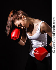 Beautiful young woman in a red boxing gloves over black...