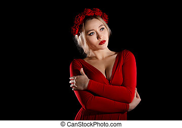 Beautiful young woman in a red dress and a rose wreath over...