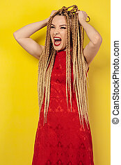 beautiful young woman in a red dress tears her hair on her head