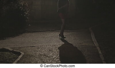 Beautiful young woman in a short skirt and heels standing in a dark park alone at night