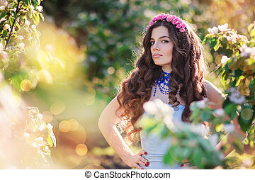 beautiful young woman in a spring park with wreath