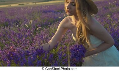 Beautiful young woman in a straw hat enjoying the scent of lavender in a field on sunset