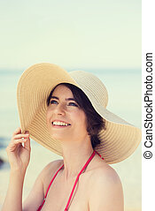 Beautiful young woman in a straw sunhat