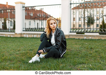 Beautiful young woman in a trendy jacket, black jeans and white shoes resting on the grass.