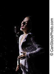 Beautiful young woman in an evening dress sings into a vintage microphone against the background of falling snow in a dark studio. Close up.