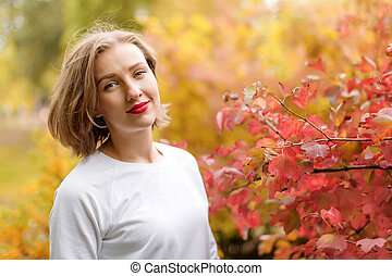 Beautiful young woman in autumn park. Season and people...