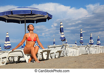 beautiful young woman in bathing suit sitting on white chaise lounge and sunbathe, rows of white loungers and blue umbrellas