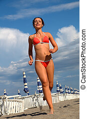 beautiful young woman in bathing suit runs on sand on beach, rows of white loungers and blue umbrellas
