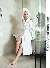 Beautiful young woman in bathrobe and towel on her head - ...
