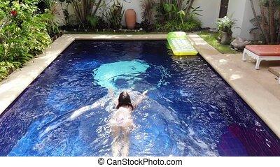 Beautiful young woman in bikini goes into a swimming pool...