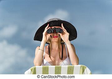 Beautiful young woman in bikini looking through binoculars at th