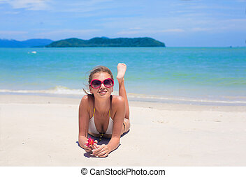 beautiful young woman  in bikini lying on tropacal beach