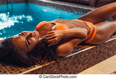 Beautiful young woman in bikini swimsuit lying on swimming pool edge.