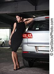 Beautiful young woman in black dress standing near her car