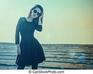 Beautiful young woman in black dress standing on beach