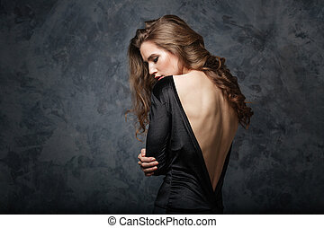 Beautiful young woman in black dress with open back