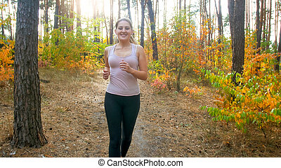Beautiful young woman in black leggings jogging in forest