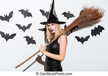 Beautiful young woman in black witch halloween costume with broom