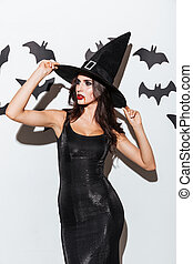 Beautiful young woman in black witch halloween costume with hat