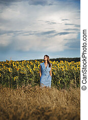 Beautiful young woman in blue dress standing on sunflower field