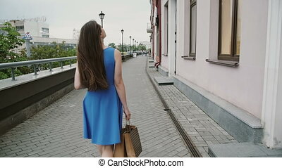 Beautiful young woman in blue dress walking in the city with shopping bags, back view, slow mo stedicam shot