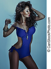 Beautiful young woman in blue swimsuit