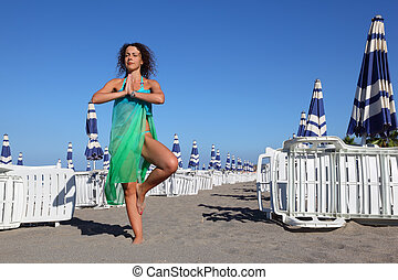 beautiful young woman in blue swimsuit and pareo stands on beach, rows of white deck chairs and beach umbrellas