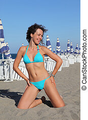 beautiful young woman in blue swimsuit kneeling on beach. in background rows of white deck chairs and beach umbrellas