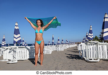 beautiful young woman in blue swimsuit and pair stands on beach. in background rows of white deck chairs and beach umbrellas