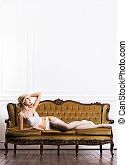 Beautiful young woman in bridal lingerie on a retro sofa