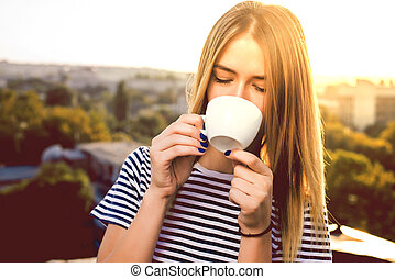 Beautiful young woman in casual wear dreaming with cup of hot coffee